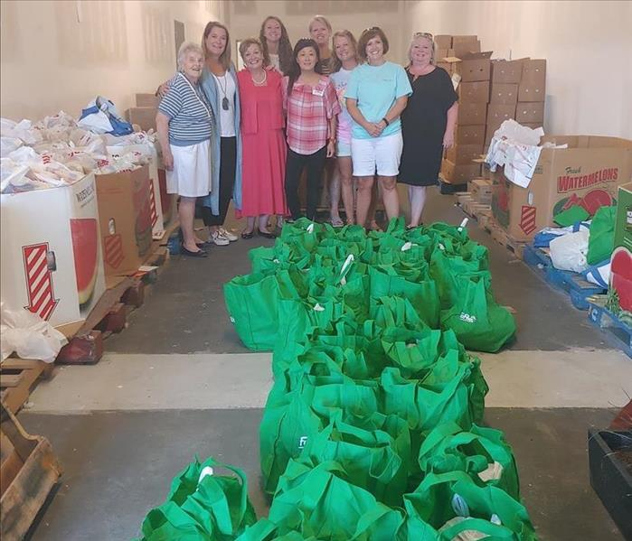 Floor filled with green bags and boxes of food. Group of women stand proudly behind showcasing their hard work.