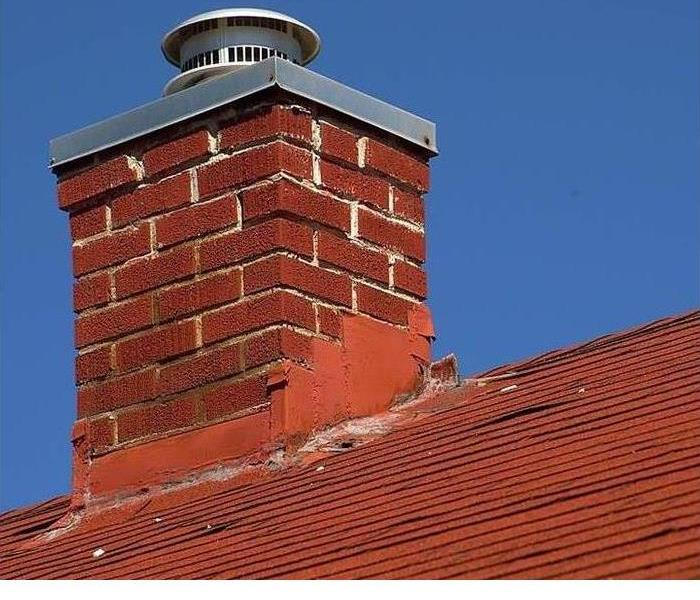 A brick chimney is shown on top of a roof