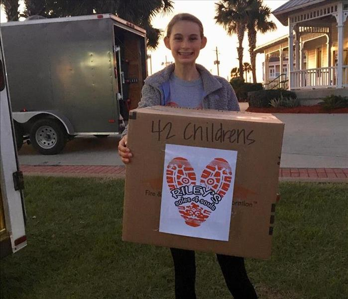 Young girl and founder of Riley's Soles 4 Souls stands proudly with a large box of donated shoes.
