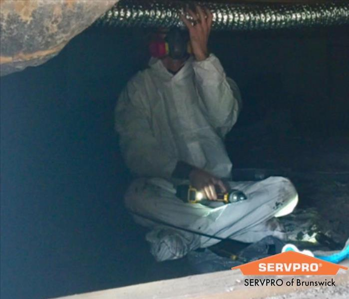 SERVPRO Mold Technician cleaning crawl space beams and is suited up in protective clothing(PPE)