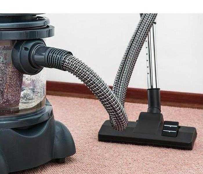 A vacuum cleaner is shown with extension hose
