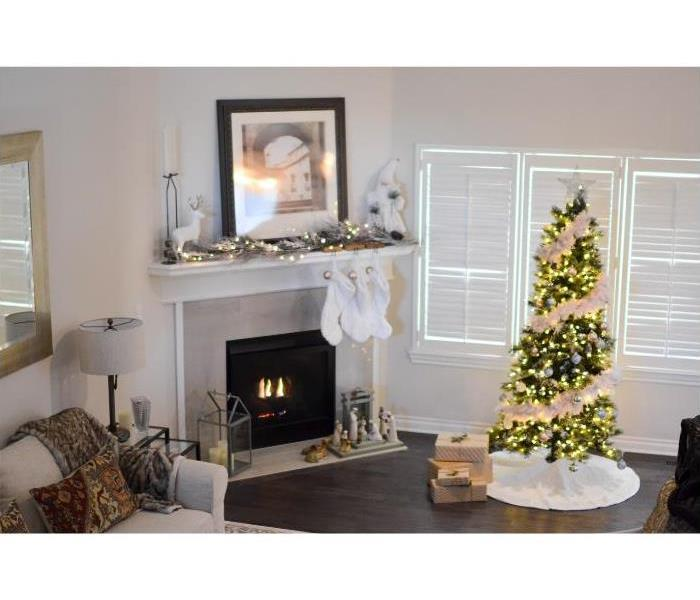 Living room painted white with stockings hung on fire place and small Christmas tree lit up.