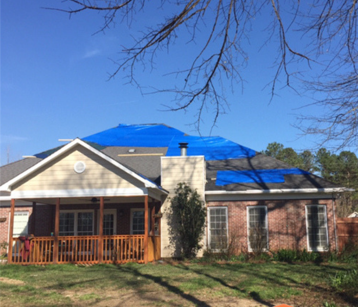 Brick house with blue tarp on roof.