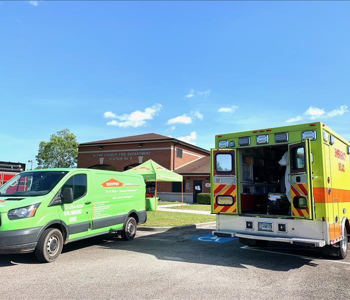 SERVPRO green van next to bright yellow ambulance after a wipe down and disinfecting mist.